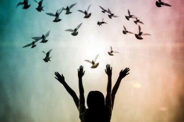 mujer-con-los-brazos-arriba-y-palomas-alrededor